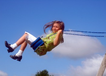 Girl swinging high in a swing