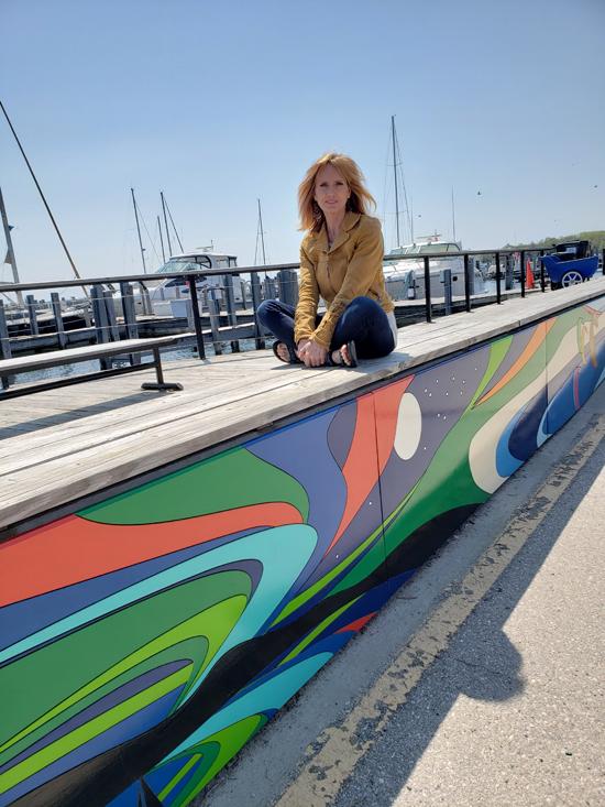 Kat Dakota sitting on Northport Marina Wall Mural